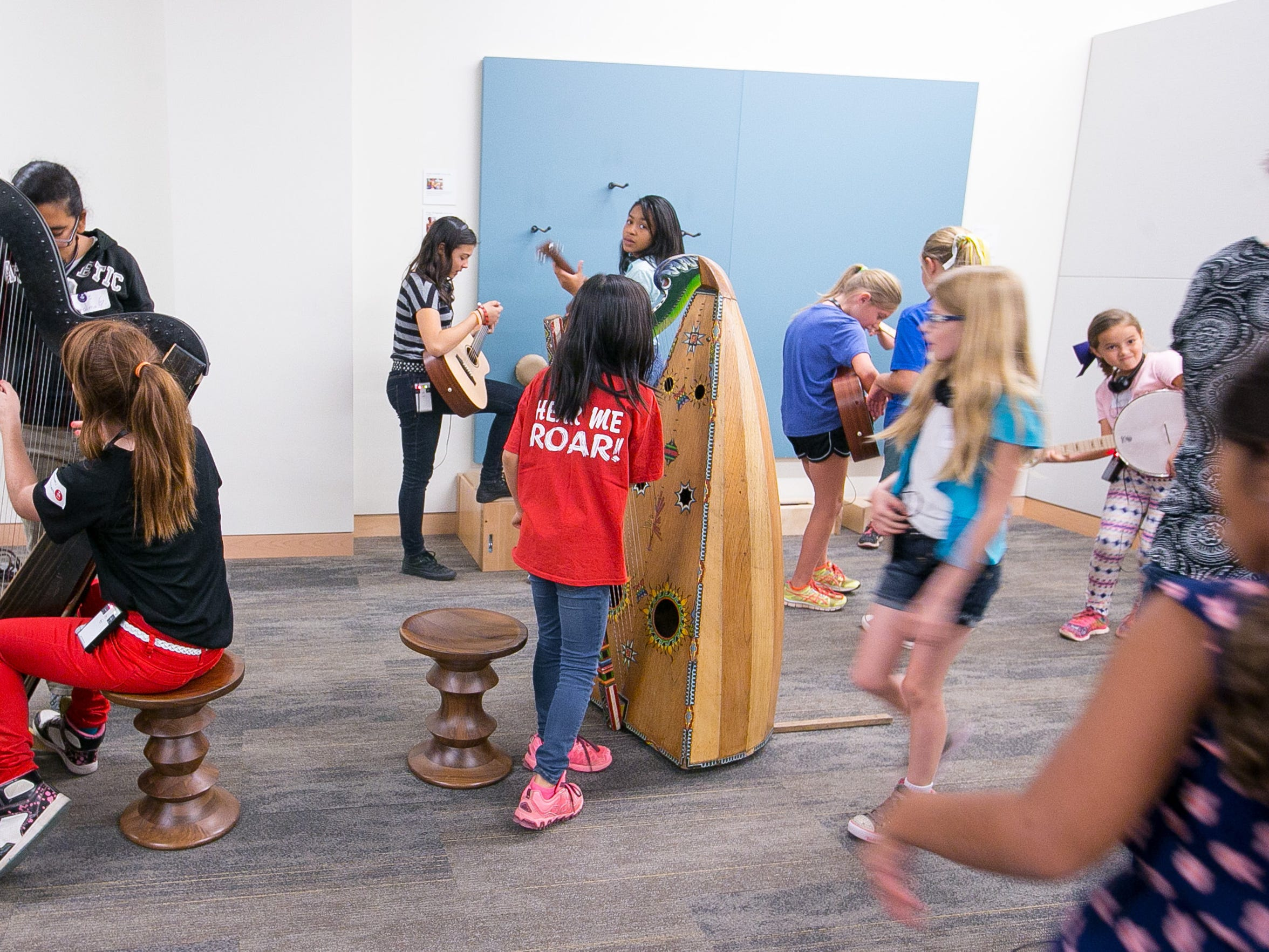 Children on a field trip play with various instruments