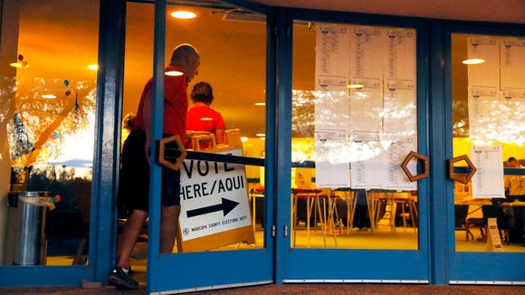 Poll marshall Steve Coulter pulls signs at the polling site at Ascension Lutheran Church after polls closed Tuesday, Aug. 30, 2016, in Paradise Valley.