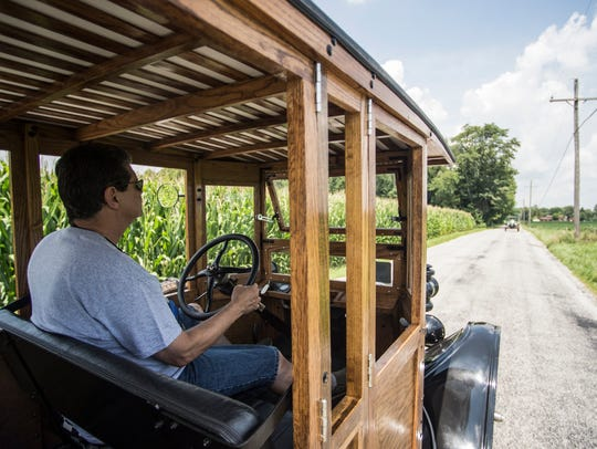 A Ford Model T travels a road in rural Rush County