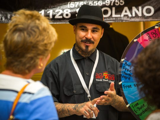 Marlo Flores, center, an employee at South West Vape, talks to potential customers during the Southern New Mexico Medical Cannabis Expo at the Hotel Encanto de Las Cruces, June 24, 2016.