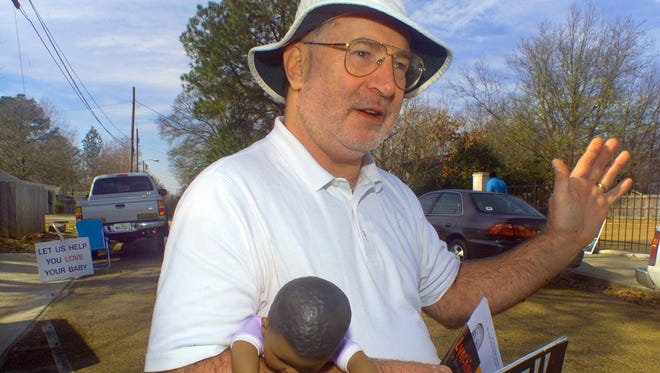 In this 2004 file photograph, Roy McMillan, an executive with the Christian Action Group, stood outside the Jackson Women's Health Organization using signs, literature and baby dolls to raise awareness for his anti-abortion stance.