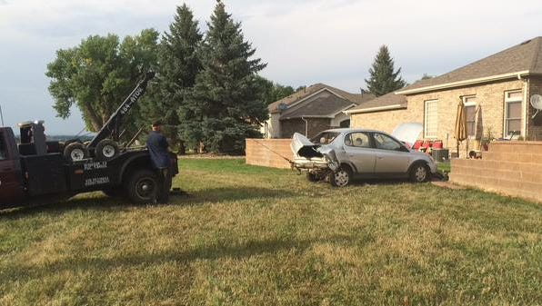 A Toyota Echo gets towed after smashing into a fence off Larimer County Road 5 in Windsor during  three-vehicle crash.