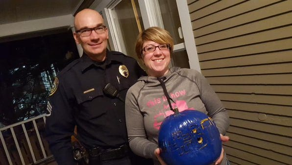 """Great Falls Police Sgt. Tony Munkres poses with  local resident Jamie Laabs, who carved a """"Back the Blue"""" pumpkin to show support for police officers."""