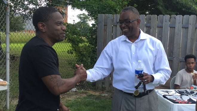 Community organizer Edward Harrison (left) shakes hands with a guest at a New Castle-area kickoff party Sunday afternoon for Building Bulls, an organization that aims to mentor youth.