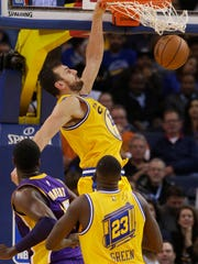 Golden State Warriors center Andrew Bogut, top, dunks against the Los Angeles Lakers during the first half. The Warriors defeated the Lakers 111-77 to start the season 16-0.