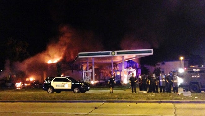 Authorities respond near a burning gas station as dozens of people protest following the fatal shooting of a man in Milwaukee, Saturday, Aug. 13, 2016.