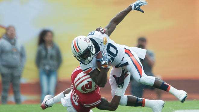 Wisconsin cornerback Darius Hillary (5) tackles Auburn wide receiver Marcus Davis (80) during the Outback Bowl between Auburn and Wisconsin at Raymond James Stadium in Tampa, Fla., on Thursday, Jan. 1, 2015.
