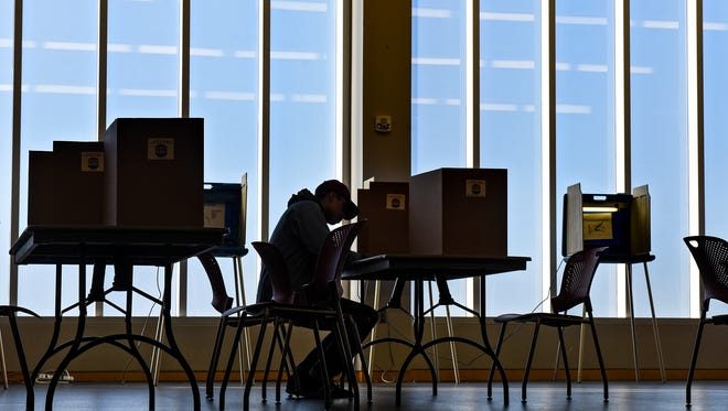 A voter completes a ballot during a quieter time late in the morning Tuesday, Nov. 8, at the St. Cloud Public Library in St. Cloud.