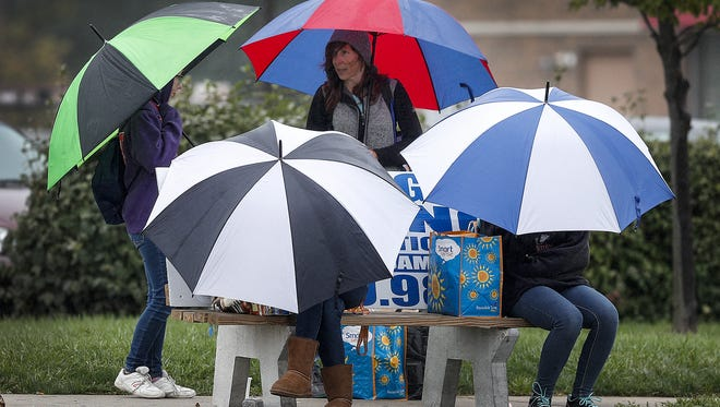 When it rains it pours, at the bus stop. Four people with similar umbrellas stay dry as they wait for the bus stop at the corner of S Emerson Ave. and E Elenor Street on Indianapolis's southeast side Wednesday, Oct 11, 2017. The next possible chance for rain in central Indiana will be this Sunday.