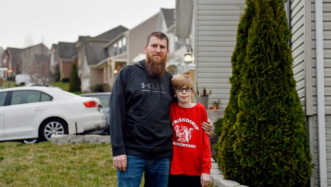 Joe Kirby, 34, stands for a portrait with his son, Joey, 10, outside their home in Codorus Township. After Kirby and his wife, Christina, failed to pay their trash bill to Penn Waste and were taken to court, the company sent a deputy sheriff to the house. He took inventory of their possessions to eventually sell at a sheriff's sale.  Penn Waste has used the process of filing a writ of execution more than 250 times since 2016.
