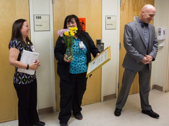Linda Perez, center, holds her award and some flowers during a short recognition ceremony at the VA Clinic on Don Roser Drive, Tuesday January 24, 2017. As Crystal Davis-Whited,left, and Michael Amaral, right, director of the El Paso VA system stand at her side.