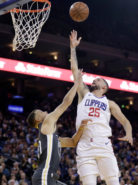 Los Angeles Clippers' Austin Rivers (25) scores over Golden State Warriors' Stephen Curry during the first half of an NBA basketball game Thursday, Feb. 22, 2018, in Oakland, Calif. (AP Photo/Marcio Jose Sanchez)