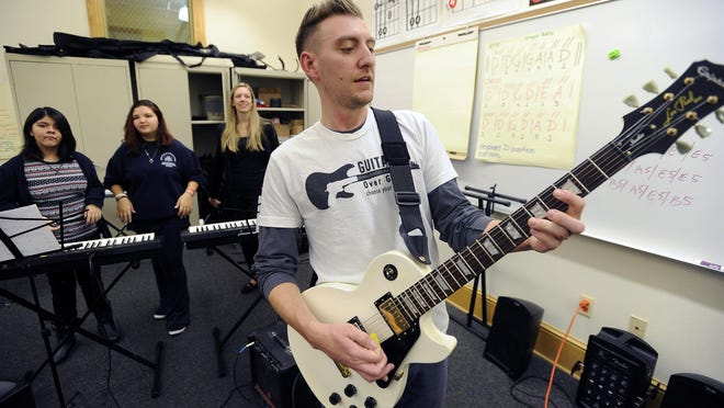 Phil Jacobson plays guitar as part of the Chicago chapter of Guns over Guitars at the Evergreen Academy in Chicago. Jacobson and friends are teaching music to inner-city kids through the program that pairs professional musicians with at-risk kids.