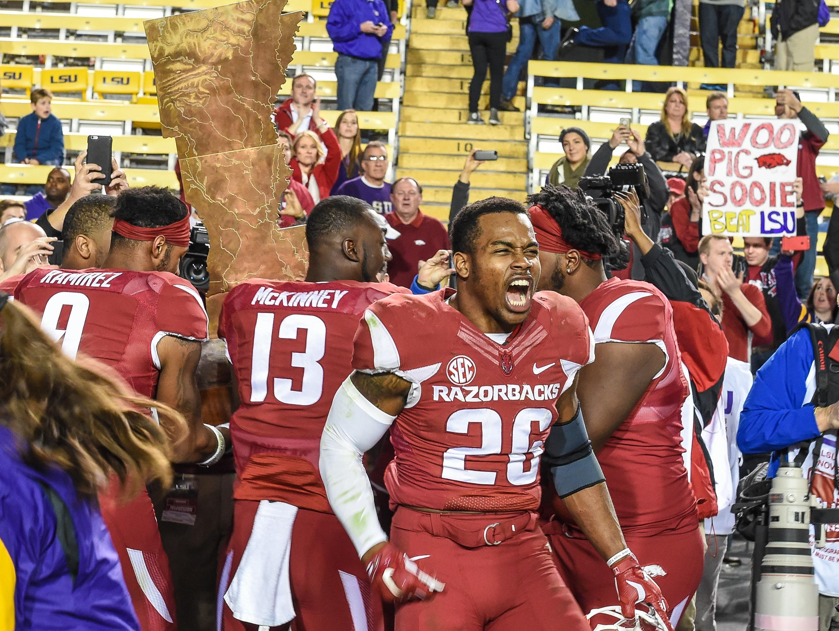 Arkansas defensive back Rohan Gaines (26) and teammates celebrate with The Golden Boot after winning a game against LSU on Saturday.