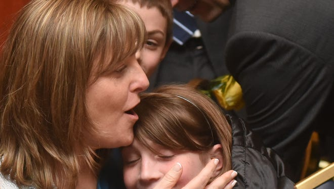 Julia Hill, Worcester County Teacher of the Year, hugs her daughter, Micah Hill as her son, Tirzah Hill, and husband Trevor Hill, look on after winning the honor at the 30th annual Worcester County Public Schools Teacher of the Year Banquet Friday, April 7, 2017 at the Clarion Resort Fontainebleau Hotel in Ocean City. (Special to The Daily Times/Todd Dudek)