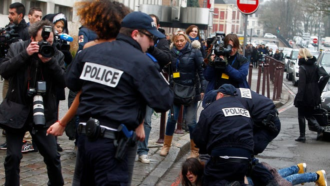 A Femen activist is held down as another is taken away by police officers during their protest Feb. 10 in front of the Lille courthouse in northern France.
