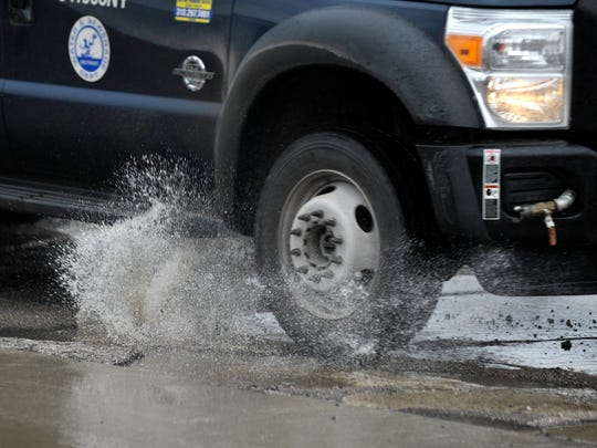 This City of Detroit work truck hits a water-filled pothole. XXXXMotorists try to maneuver around water-filled potholes on southbound Mound Rd.  between Charles and Talbot in Detroit, Tuesday afternoon, February 20, 2018. (Todd McInturf, The Detroit News)2018.