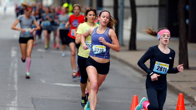 Runners in the WomenÕs Competitive Division of the Grand Blue Mile make their way down Locust St. Tuesday, April 21, 2015.