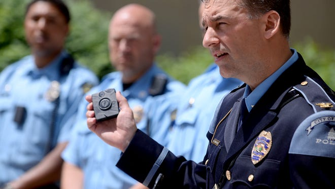 Lansing Police Chief Michael Yankowski holds one of the three models of body cameras Monday, June 1, 2015, as he speaks during a press conference announcing the department's pilot program to test the different models.