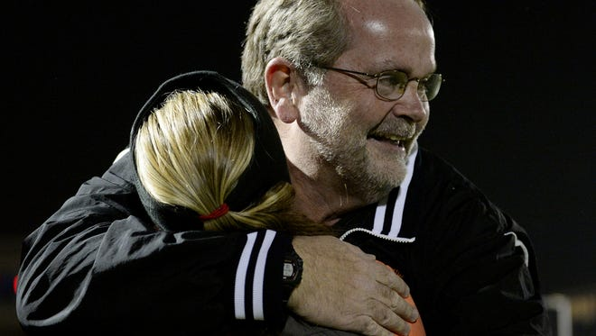Palmyra assistant coach Kent Harshman embraces his daughter and head coach Kristi Costello after the field hockey team defeated Emmaus 4-0 during the PIAA AAA semifinal game at Tulpehocken High School on Tuesday, November 11, 2014.  On Thursday, Harshman was hired to take over the head coaching job from Costello, who resigned earlier this year to spend more time with her husband and two young children.