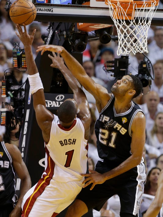 San Antonio Spurs forward Tim Duncan (21) blocks a shot to the basket by Miami Heat center Chris Bosh (1), during the first half in Game 4 of the NBA basketball finals, Thursday, June 12, 2014, in Miami.  (AP Photo/Lynne Sladky)