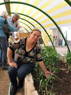 Promotora Juana Flores shows a variety of fresh vegetables that grow year around in one of the community greenhouses located next door to the public library in Palomas, Mexico. Border Partners board members Helena Myers and Paul Dulin stand in the background.