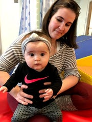 Sarah Scanlan helps her daughter Mara Kate with physical therapy as part of her recovery from open heart surgery to repair four congenital heart defects.