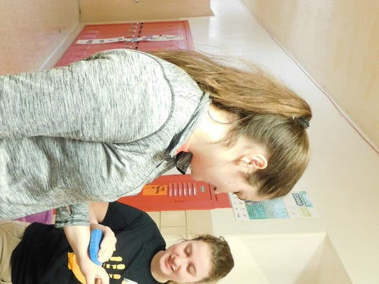 Marissa Overmyer, left, allows Liza Quick to apply a temporary tattoo to her hand Wednesday morning at Fremont Ross High School during 'Kick Butts Day.'