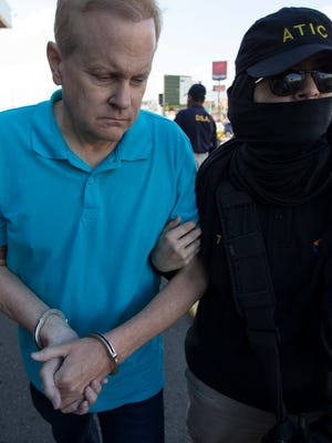 Eric Conn is escorted by SWAT team agents prior to his extradition, at the Toncontin International Airport, in Tegucigalpa, Honduras, Tuesday, Dec. 5, 2017. Conn, a fugitive Kentucky lawyer who escaped before facing sentencing for his central role in a massive Social Security fraud case, was captured as he came out of a restaurant in the coastal city of La Ceiba, on Monday.