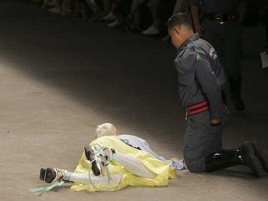 Model Tales Soares lies on the catwalk as a paramedic tends to him after he collapsed during Sao Paulo Fashion Week in Sao Paulo, Brazil, Saturday, April 27, 2019.