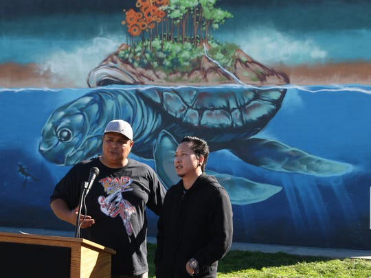 Joseph Frausto, executive director of Salinas Urban Arts Project, stands with mural painter Lee Abellana at the dedication ceremony of the mural at La Paz Park, Salinas