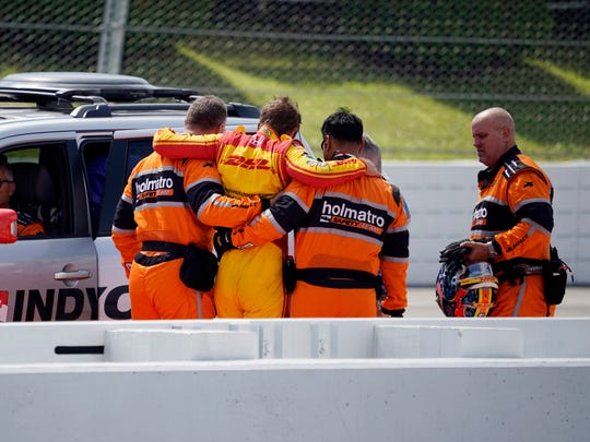 Ryan Hunter-Reay is helped from his car after wrecking during qualifying for Sunday's IndyCar auto race, Saturday, Aug. 19, 2017, in Long Pond, Pa. (AP Photo/Matt Slocum)