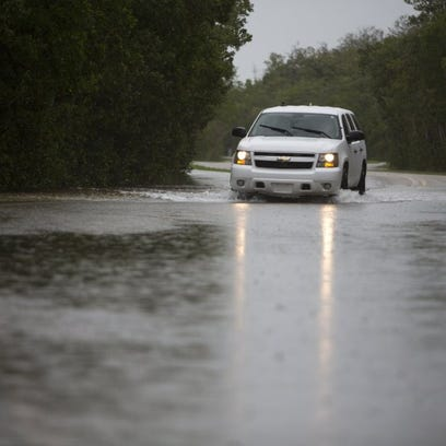 An SUV drives through flooding on Goodland Road in