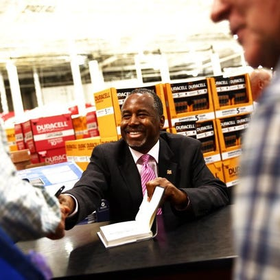 Republican presidential candidate Ben Carson signs books Wednesday at Costco in North Naples. (Dorothy Edwards/Staff )