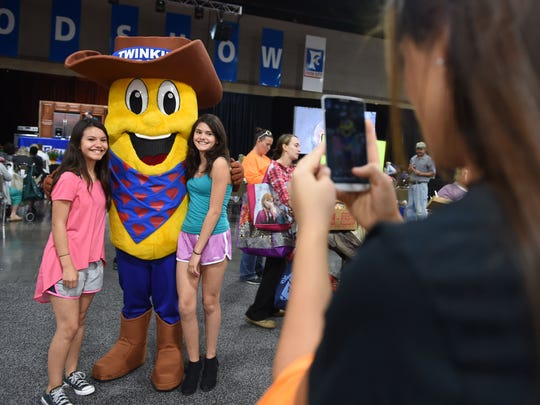 Guests pose with the Twinkie mascot during the Food City Food Show at the Knoxville Convention Center in this October 2016 file photo.
