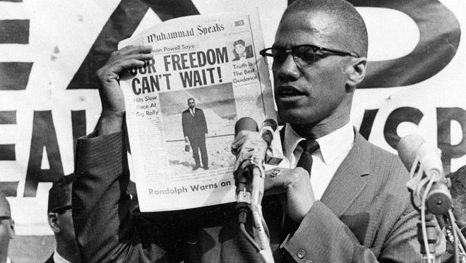 Black Muslim leader Malcolm X holds up a paper for the crowd to see during a Black Muslim rally in New York City on Aug. 6, 1963.