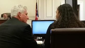Attorney William Stewart Mathews and Stephanie Bates confer before Bates' trial on felonious assault and child endangerment charges Tuesday.