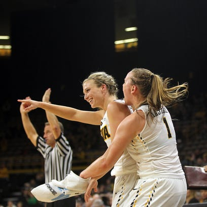 Iowa's Alexa Kastanek jumps off the bench to celebrate