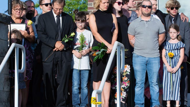 Members of the Hendrix family stand together throughout a 90-minute memorial service held Sunday evening in honor of 35-year-old Henderson County Sheriff's Deputy Ryan Hendrix, who was killed in the line of duty Thursday.