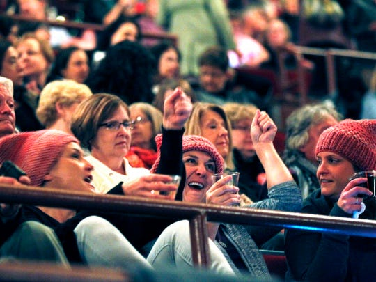 Hillary Clinton  supporters raise their glasses before Clinton tales the stage Thursday night at the Riverside Theater.