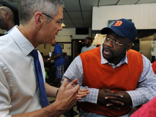 Left: Schauer talks to autoworker Leon Rice about his jobs plan during a campaign stop Sept. 7.