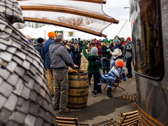 Festival goers form around a fire pit to keep warm at the New Holland Brewing Company area during the 11th annual Winter Beer Festival in Comstock Park, Mich., Friday, Feb. 26, 2016.