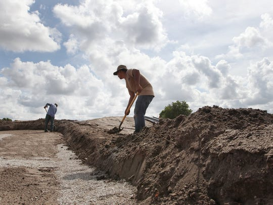 Juan Castaneda  works with other crew members while renovating the golf course near the clubhouse at the Fort Myers Country Club in June.