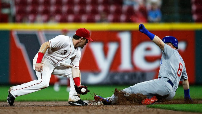 Chicago Cubs center fielder Ian Happ (8) slides in safe ahead of a tag from Cincinnati Reds second baseman Scooter Gennett (3) on a double to left field in the top of the seventh inning of the MLB National League game between the Cincinnati Reds and the Chicago Cubs at Great American Ball Park in downtown Cincinnati on Friday, May 18, 2018. The Reds lost their 30th game of the season, 8-1, to the Cubs.