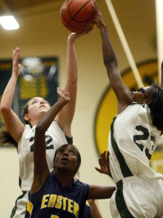 York Catholic's Marissa Ressler, left, and Japriya Carroll soar over Eastern York's Mahlet Kebede during Tuesday night's game at York Catholic. Carroll scored a game-high 19 points to lead the Fighting Irish to a 53-41 victory. (Kate Penn -- GameTimePA.com)