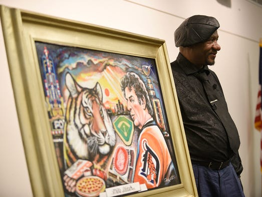Curtis Lewis poses for a photo with his painting dedicated