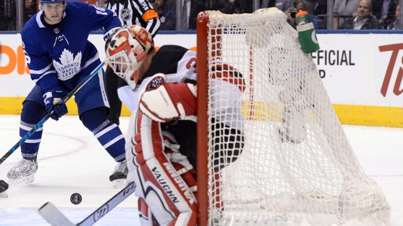 New Jersey Devils goalie Cory Schneider (35) makes a save as Toronto Maple Leafs center Mitchell Marner (16) looks for the rebound during the second period of an NHL hockey game Wednesday, Oct. 11, 2017, in Toronto. (Nathan Denette/The Canadian Press via AP)