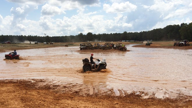 ATV drivers test their vehicles' abilities in a muddy pond at Muddy Bottoms ATV park Saturday.