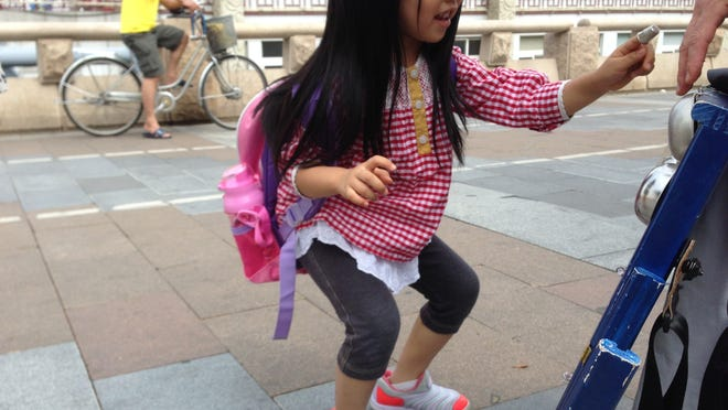 Girl playing washboard in Guangzhou, China.