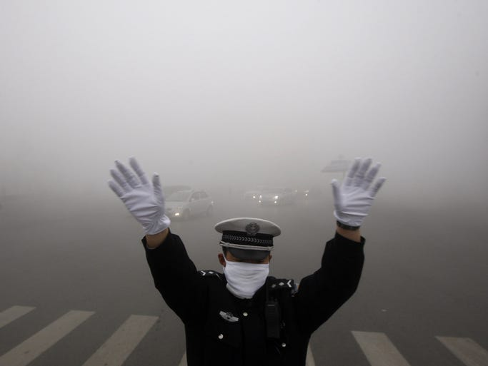 A policeman gestures as he works on a street in heavy smog in Harbin, northeast China's Heilongjiang province, on Oct. 21.